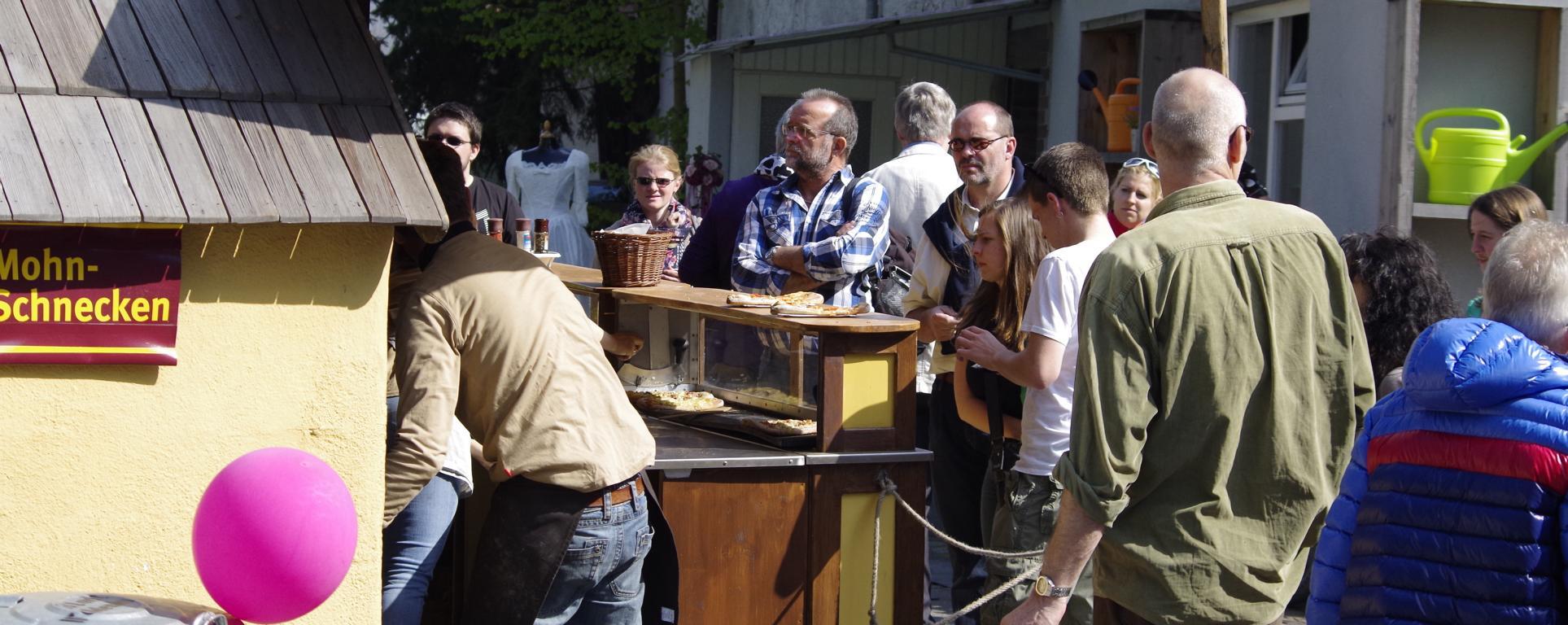 Kunden stehen vor der aulendorfer Dinnete Bäckerei - Holzofenbeck