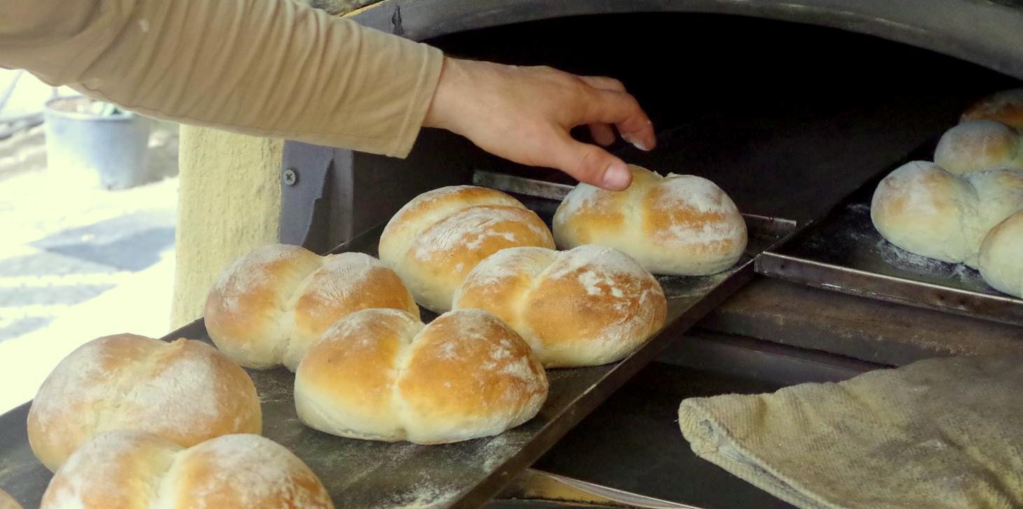 weizenbrötchen beim backen im holzofen, handschuh vor dem ofen, qualitätskontrolle ob schon fertig gebacken