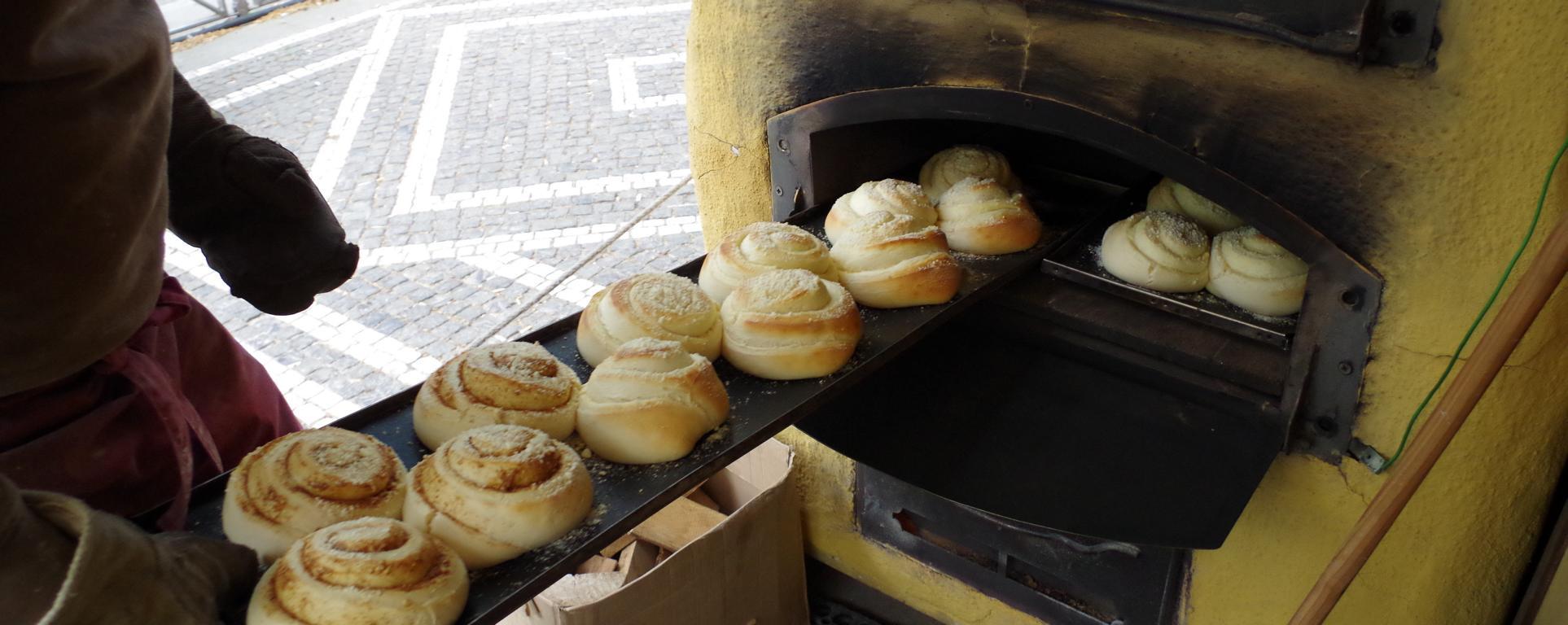 dinnete-bäcker wendet ein blech frischer hefeschnecken in einem holzofen