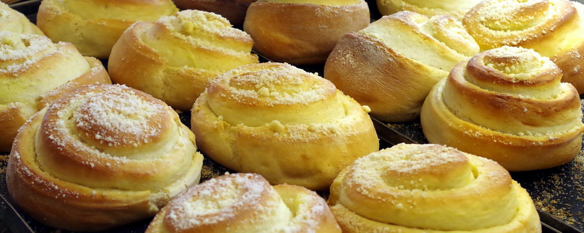 Vanilleschnecken in Reihe auf einem Blech, im Holzofen gebacken.