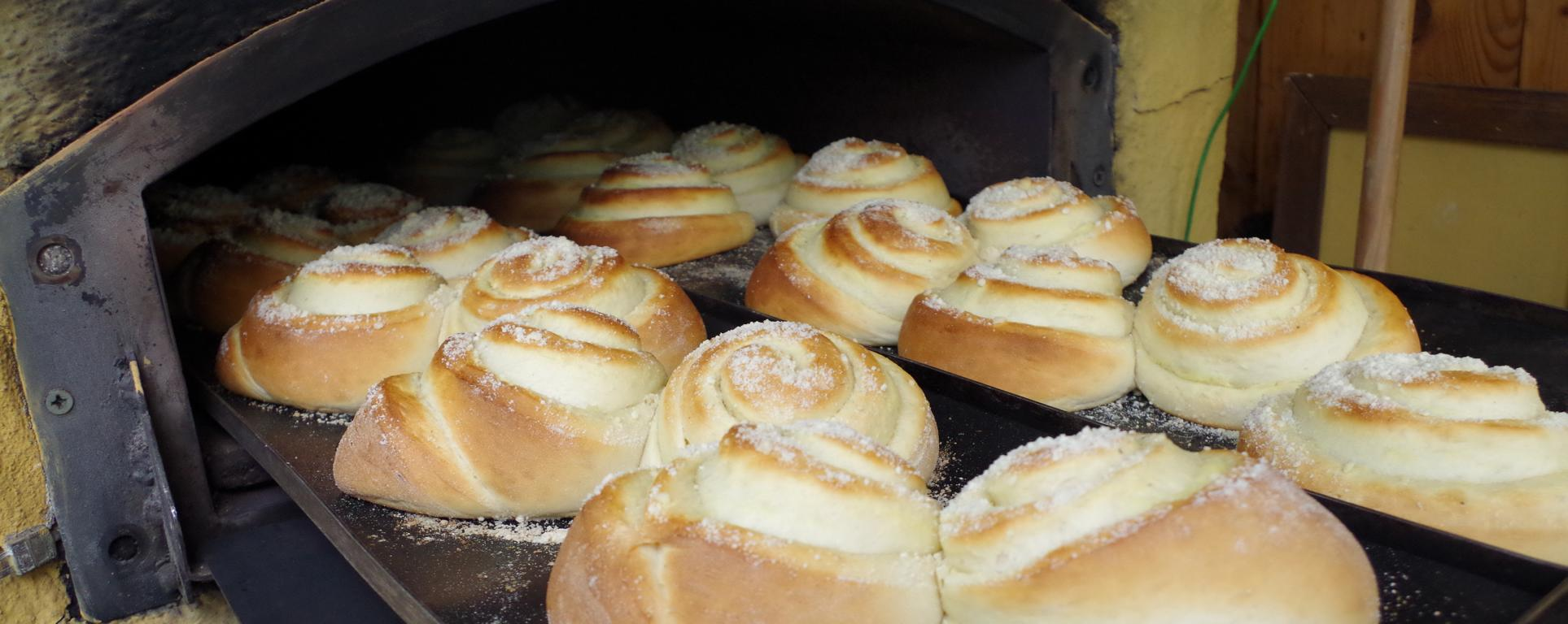 Der Dinnete-Bäcker zieht zwei fertig-gebackene bleche Puddingschnecken aus dem Holzofen